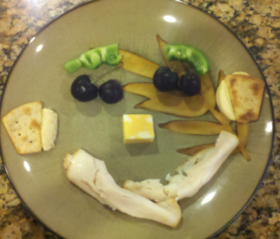eyebrows - green pepper; eyes - cherries; ears - pita chips in hummus; nose - cheese; mouth - rolled up lunch meat