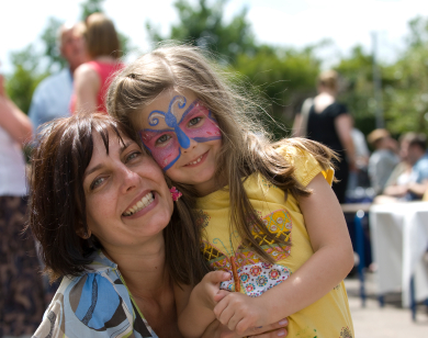 Mother and Face Painted Daughter cuddle at Fair